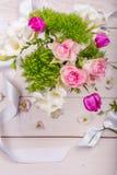 Εορταστική σύνθεση λουλουδιών στο άσπρο ξύλινο υπόβαθρο Υπερυψωμένη όψη Στοκ Εικόνα