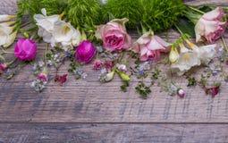 Εορταστική σύνθεση λουλουδιών στο παλαιό ξύλινο υπόβαθρο Υπερυψωμένη όψη Στοκ φωτογραφία με δικαίωμα ελεύθερης χρήσης