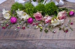 Εορταστική σύνθεση λουλουδιών στο παλαιό ξύλινο υπόβαθρο Υπερυψωμένη όψη Στοκ Εικόνες