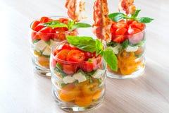 Εορταστική caprese σαλάτα με το τηγανισμένο μπέϊκον στα οβελίδια στα γυαλιά στοκ φωτογραφία με δικαίωμα ελεύθερης χρήσης