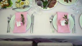 Εορταστικός γαμήλιος πίνακας που θέτει με τα ρόδινα λουλούδια, πετσέτες, γυαλιά απόθεμα βίντεο