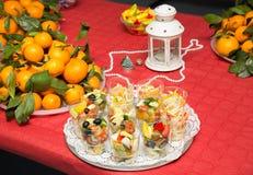 Εορταστικός εξυπηρετώντας πίνακας με τις σαλάτες και τα φρούτα Στοκ Εικόνες