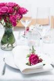 Εορταστικός να δειπνήσει πίνακας που θέτει με τα ρόδινα τριαντάφυλλα Στοκ εικόνα με δικαίωμα ελεύθερης χρήσης