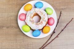 Εορταστικός πίνακας με τα ζωηρόχρωμα αυγά και cupcake Στοκ Εικόνα