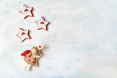 Εορταστικό θέμα διακοπών Χριστουγέννων με τον άγγελο παιχνιδιών και το κόκκινο άσπρο αστέρι τρία στοκ φωτογραφίες
