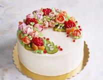 Εορταστικό κέικ με τα λουλούδια και τα φρούτα κρέμας σε ένα ελαφρύ υπόβαθρο Στοκ φωτογραφία με δικαίωμα ελεύθερης χρήσης
