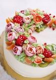 Εορταστικό κέικ με τα λουλούδια και τα φρούτα κρέμας σε ένα ελαφρύ υπόβαθρο Στοκ Φωτογραφία
