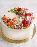 Εορταστικό κέικ με τα λουλούδια και τα φρούτα κρέμας σε ένα ελαφρύ υπόβαθρο Στοκ εικόνες με δικαίωμα ελεύθερης χρήσης