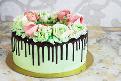 Εορταστικό κέικ με τα τριαντάφυλλα φιαγμένα από κρέμα σε ένα άσπρο ξύλινο υπόβαθρο Στοκ εικόνα με δικαίωμα ελεύθερης χρήσης