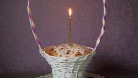 Εορταστικό κέικ Πάσχας με ένα κερί στο ψάθινο καλάθι και μερικά χρωματισμένα αυγά κατωτέρω απόθεμα βίντεο
