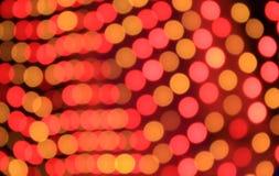 Εορταστικό κόκκινο και πορτοκαλί υπόβαθρο με την επίδραση boke Στοκ Εικόνες