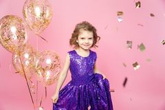 Εορταστικό μικρό κορίτσι με τα μπαλόνια στοκ φωτογραφία