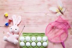 Εορταστικό σύνολο Πάσχας με τα αυγά, το λουλούδι και το κουνέλι Πάσχας, χρώμα, βούρτσα, πεταλούδα, καθαρή στον αγροτικό ξύλινο πί Στοκ εικόνες με δικαίωμα ελεύθερης χρήσης