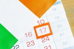 Εορταστικό υπόβαθρο ημέρας του ST Πάτρικ ` s Ιρλανδική σημαία που καλύπτει το ημερολόγιο με το πλαισιωμένο στις 17 Μαρτίου Στοκ φωτογραφία με δικαίωμα ελεύθερης χρήσης