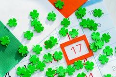 Εορταστικό υπόβαθρο ημέρας του ST Πάτρικ ` s Πράσινα quatrefoils και ιρλανδική σημαία που καλύπτουν το ημερολόγιο με το πλαισιωμέ Στοκ Εικόνες