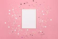 Εορταστικό υπόβαθρο με το κενό άσπρο πλαίσιο φωτογραφιών στο ροζ με το κομφετί στοκ φωτογραφία