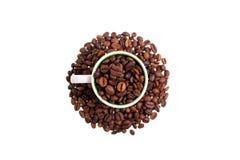Επάνω από την άποψη ενός φλυτζανιού καφέ που γεμίζουν με τα φασόλια coffe Στοκ Εικόνες