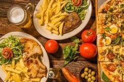 Επάνω από την άποψη της ομάδας γρήγορου γεύματος, ψημένης στη σχάρα μπριζόλας βόειου κρέατος και λαμπτήρων, πίτσας και τηγανισμέν Στοκ Φωτογραφία