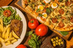 Επάνω από την άποψη της ομάδας γρήγορου γεύματος, ψημένων στη σχάρα potatos βόειου κρέατος, πιτσών και τηγανητών, με τις ντομάτες Στοκ εικόνες με δικαίωμα ελεύθερης χρήσης