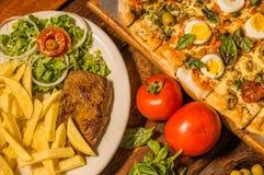 Επάνω από την άποψη της ομάδας γρήγορου γεύματος, ψημένων στη σχάρα potatos βόειου κρέατος, πιτσών και τηγανητών, με τις ντομάτες Στοκ φωτογραφία με δικαίωμα ελεύθερης χρήσης