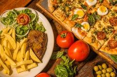 Επάνω από την άποψη της ομάδας γρήγορου γεύματος, ψημένων στη σχάρα potatos βόειου κρέατος, πιτσών και τηγανητών, με τις ντομάτες Στοκ εικόνα με δικαίωμα ελεύθερης χρήσης