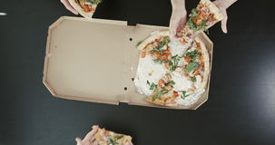 Επάνω από την άποψη των χεριών που παίρνουν το pazza Πεδίο που τοποθετείται στο σκοτεινό πίνακα κατανάλωση της πίτσας φίλ&omeg απόθεμα βίντεο