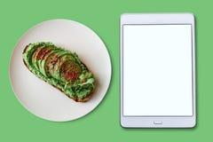 επάνω από την όψη Ταμπλέτα με την κενή οθόνη για το κείμενο Έπειτα είναι μια εύγευστη και υγιής χορτοφάγος φρυγανιά ή ένα αβοκάντ Στοκ εικόνες με δικαίωμα ελεύθερης χρήσης