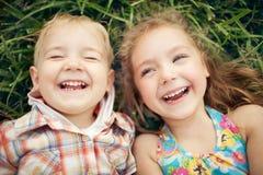 Επάνω από το πορτρέτο άποψης δύο ευτυχών χαμογελώντας παιδιών που βρίσκεται στην πράσινη χλόη Στοκ εικόνες με δικαίωμα ελεύθερης χρήσης