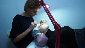 Επέκταση Eyelash Ο κύριος καλλιτέχνης σύνθεσης επεκτείνεται eyelashes σε ένα νέο κορίτσι Το κορίτσι ξαπλώνει Ένας λαμπτήρας είναι φιλμ μικρού μήκους