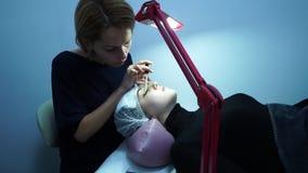 Επέκταση Eyelash Ο κύριος καλλιτέχνης σύνθεσης επεκτείνεται eyelashes σε ένα νέο κορίτσι Το κορίτσι ξαπλώνει Ένας λαμπτήρας είναι απόθεμα βίντεο