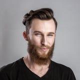 Επίβουλος και πανούργος νεαρός άνδρας που απομονώνεται στο γκρίζο υπόβαθρο Στοκ Εικόνα