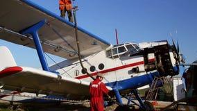 Επίγειο πλήρωμα αεροσκαφών που προσθέτει τα καύσιμα παλαιό ρωσικό biplane απόθεμα βίντεο
