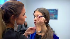 Επίδειξη μόδας, εργασία visagist, που κάνει επαγγελματικός να αποτελέσει, παρασκήνια όμορφο πρόσωπο του θηλυκού προτύπου κοριτσιώ φιλμ μικρού μήκους