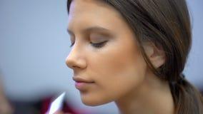 Επίδειξη μόδας, εργασία visagist, που κάνει επαγγελματικός να αποτελέσει, παρασκήνια όμορφο πρόσωπο του θηλυκού προτύπου κοριτσιώ απόθεμα βίντεο