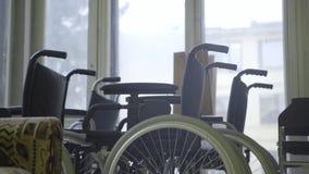 Επίδειξη της δέσμης των αναπηρικών καρεκλών με τις άσπρες ρόδες που τίθεται δίπλα στα παράθυρα απόθεμα βίντεο