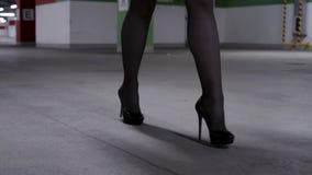 Επίδειξη των ποδιών της περπατώντας γυναίκας στις μαύρες γυναικείες κάλτσες, υψηλά τακούνια στο γκαράζ απόθεμα βίντεο