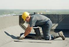 Επίπεδη στέγη που καλύπτει τις εργασίες με το υλικό κατασκευής σκεπής αισθητές στοκ φωτογραφία