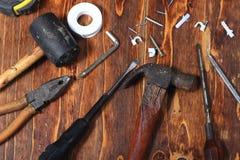 Επίπεδος βάλτε ή βρώμικο διαβρωτικό σφυρί τοπ άποψης, κατσαβίδι, καρφί, ψαράς, σφραγίδα, πιό plier στο σκοτεινό ξύλινο πίνακα Στοκ Εικόνες