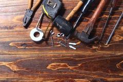 Επίπεδος βάλτε ή βρώμικο διαβρωτικό σφυρί τοπ άποψης, κατσαβίδι, καρφί, ψαράς, σφραγίδα, πιό plier στο σκοτεινό ξύλινο πίνακα Στοκ φωτογραφία με δικαίωμα ελεύθερης χρήσης