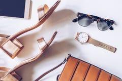 Επίπεδος βάλτε ενός ελάχιστου συνόλου θηλυκών εξαρτημάτων: χρυσό wristwatch, μέσα σανδάλια τακουνιών με το λουρί αστραγάλων, τσάν στοκ εικόνα με δικαίωμα ελεύθερης χρήσης