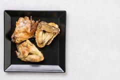 Επίπεδος βάλτε επάνω από το μαύρο πιάτο με τα τηγανισμένα φτερά κοτόπουλου στον άσπρο μαρμάρινο πίνακα Στοκ φωτογραφία με δικαίωμα ελεύθερης χρήσης