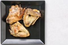Επίπεδος βάλτε επάνω από το μαύρο πιάτο με τα τηγανισμένα φτερά κοτόπουλου στον άσπρο μαρμάρινο πίνακα Στοκ εικόνα με δικαίωμα ελεύθερης χρήσης