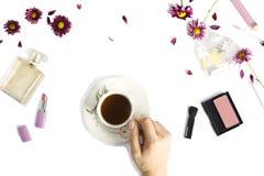 Επίπεδος βάλτε με τα μπουκάλια του αρώματος, η γυναίκα αποτελεί τα προϊόντα, τα λουλούδια και το φλυτζάνι του τσαγιού στοκ εικόνες