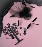 Επίπεδος βάλτε με το θηλυκό Μαύρο εξαρτημάτων εξαρτήσεων συλλογής κομμάτων αποκριών στο ανοικτό ροζ υπόβαθρο: κόσμημα, καπέλο με  στοκ εικόνα