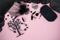 Επίπεδος βάλτε με το θηλυκό Μαύρο εξαρτημάτων εξαρτήσεων συλλογής κομμάτων αποκριών στο ανοικτό ροζ υπόβαθρο: κόσμημα, καπέλο με  στοκ εικόνες με δικαίωμα ελεύθερης χρήσης