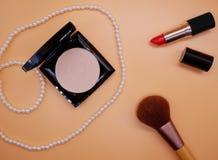 Επίπεδος βάλτε τα καλλυντικά και τα εξαρτήματα στο ανοικτό πορτοκαλί υπόβαθρο Στοκ Φωτογραφία