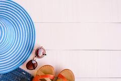 Επίπεδος βάλτε τα μπλε γυαλιά ηλίου καπέλων και το παπούτσι πουκάμισων στον άσπρο ξύλινο πίνακα Στοκ φωτογραφίες με δικαίωμα ελεύθερης χρήσης