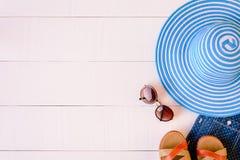 Επίπεδος βάλτε τα μπλε γυαλιά ηλίου καπέλων και το παπούτσι πουκάμισων στον άσπρο ξύλινο πίνακα Στοκ εικόνες με δικαίωμα ελεύθερης χρήσης
