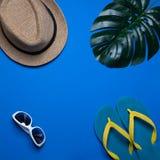 Επίπεδος βάλτε τα ταξιδιωτικά εξαρτήματα στο μπλε υπόβαθρο με το καπέλο, τα γυαλιά ηλίου, το τοπ ταξίδι άποψης ή την έννοια διακο στοκ εικόνες