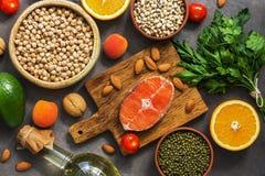 Επίπεδος βάλτε τα υγιή ισορροπημένα ακατέργαστα τρόφιμα, το σολομό, τα όσπρια, τα λαχανικά, τα φρούτα, τα πράσινα και τα καρύδια  στοκ εικόνες